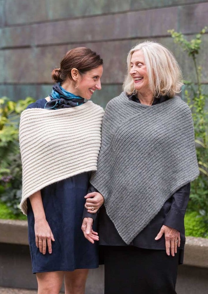 Two women wearing knitted ponchos
