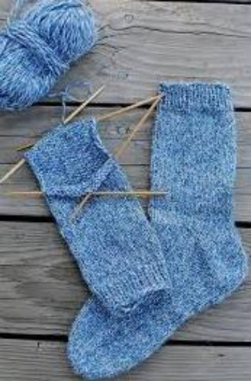 A pair of light blue, knitted socks on needles