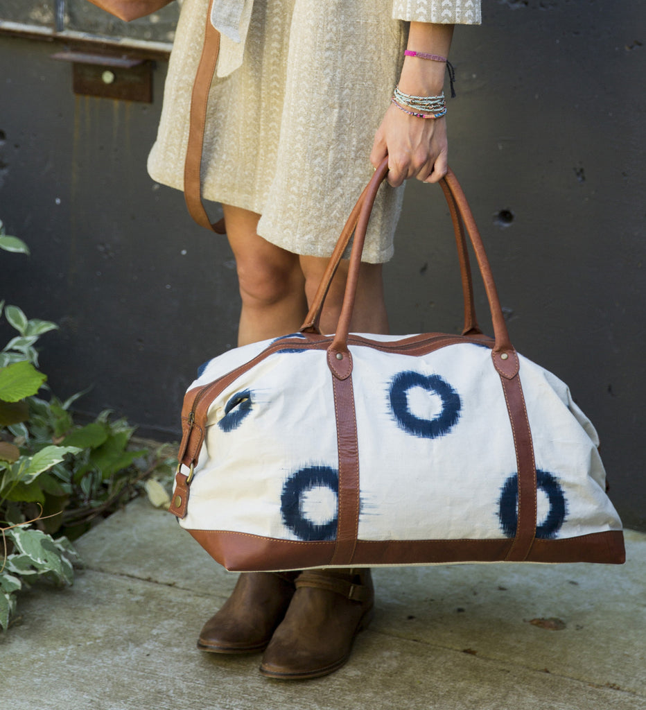 Hand-Loomed Ikat White Fabric Duffle Bag with Navy Circle Pattern and Brown Leather Lining and Handles. Zipper Closure.