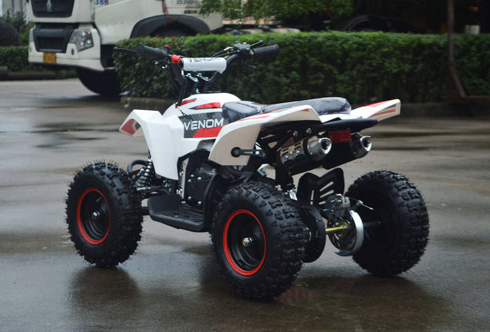 49cc Mini Quad ATV in red/white combo parked diagonally facing its rear to the left revealing dual exhaust pipes and free matching rims in red