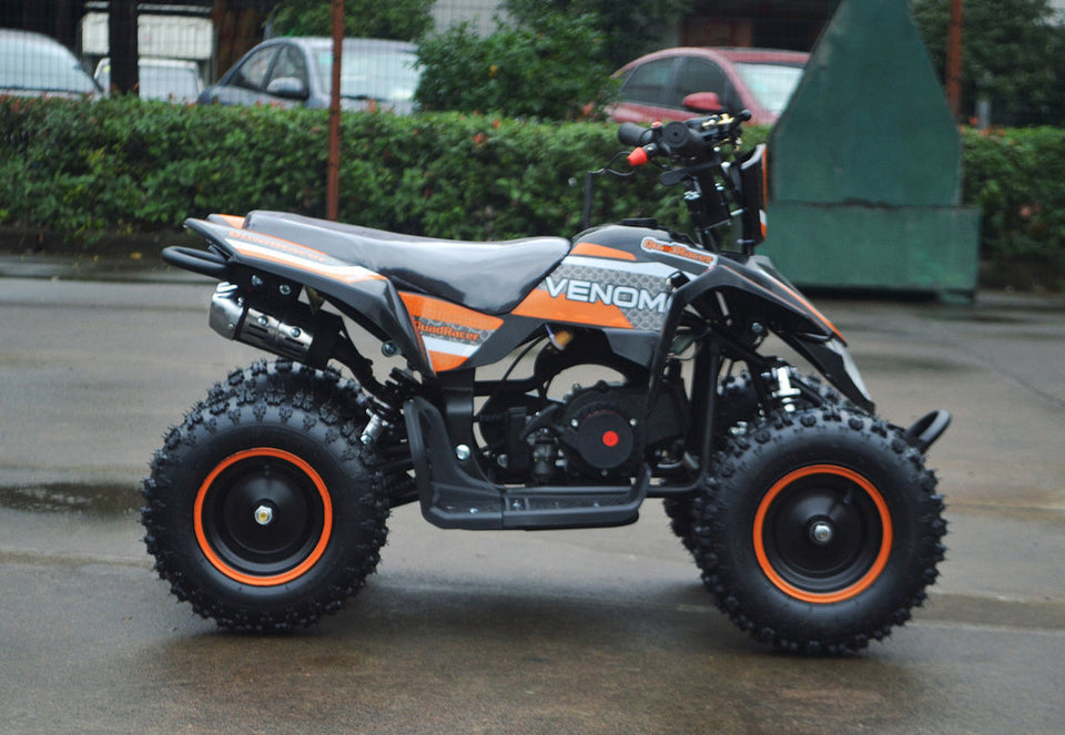49cc Mini Quad ATV in orange/black combo parked sideways revealing right side / metal pull start side of ATV