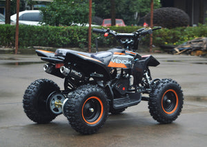 49cc Mini Quad ATV in orange/black combo parked diagonally facing its rear to the right side / aluminum pull start side of the ATV