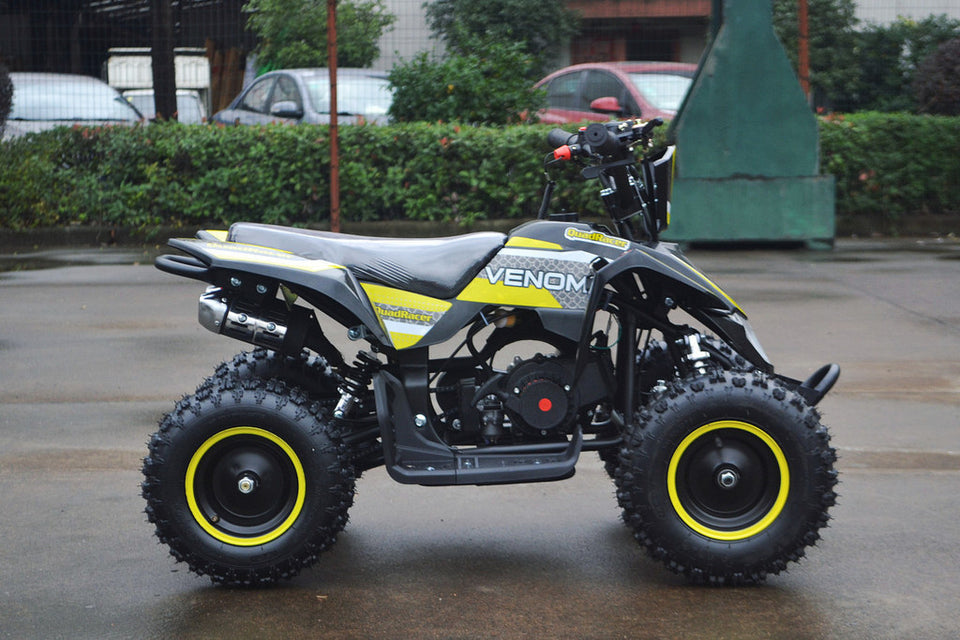 49cc Mini Quad ATV in yellow/black combo parked sideways revealing right side of ATV when sitting on it. Metal Pull Start and 49cc engine revealed.