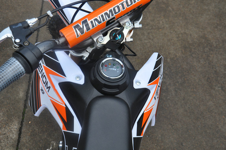 Sitting down view of Orange and white fully electric dirt bike 500 watts 24 volts. Battery indiactor, key switch indicator, handle bars are revealed.