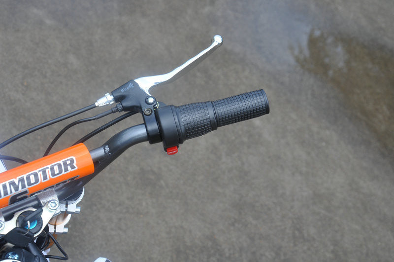 Close up of right throttle handle of Orange and white fully electric dirt bike 500 watts 24 volts with on/off button and right hand brake revealed