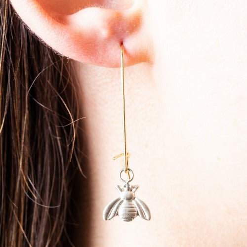 silber bee shape earrings with a long gold hoop.