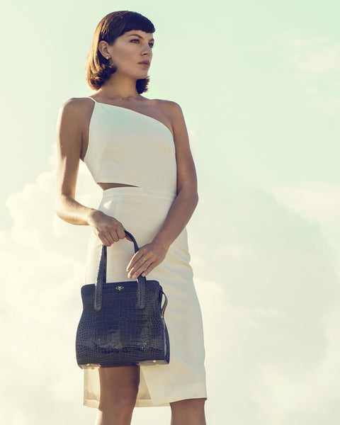 Model powerful feminine holding with confidence YB ADAM S TOTE Genuine American Alligator Charcoal Grey Model White Elegant Dress Big Sky Clouds Background