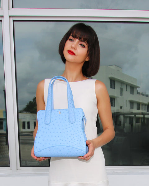 Pretty Model holding with both hands Sky Cool Blue Ostrich Genuine Sustainable Adam Small Tote Yara Bashoor with Art Deco Building reflected on window