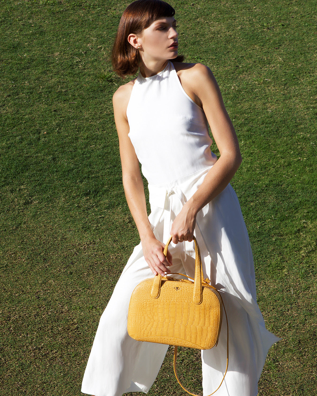 YB Charlie L Model in white posing with matte finish Golden Buttercup Alligator Tote