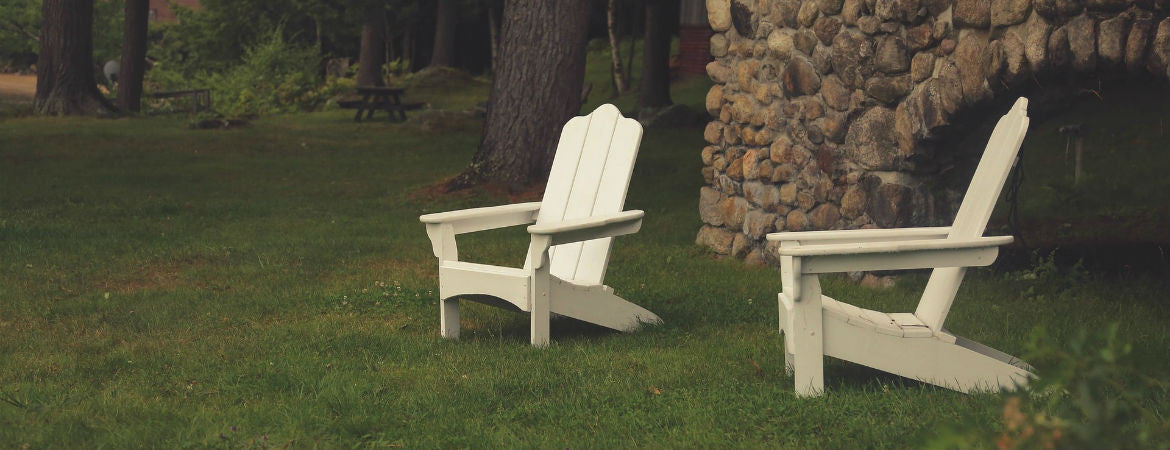 two white chairs by an outdoor fireplace