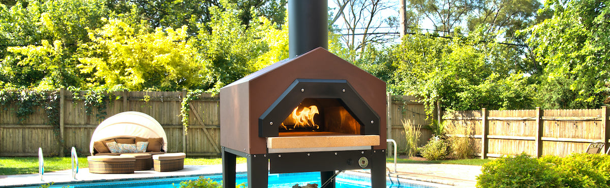 Gas pizza oven sitting in a backyard in front of a pool