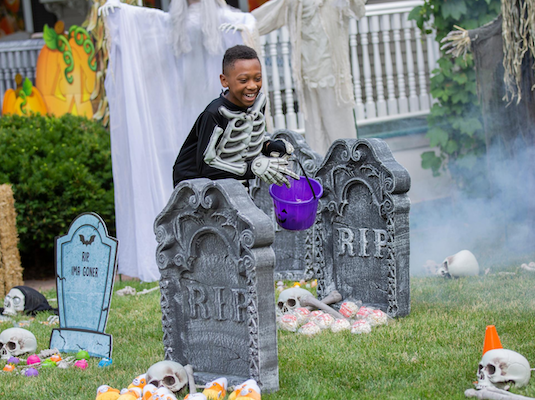 Boy on a Halloween scavenger hunt in a pretend cemetary
