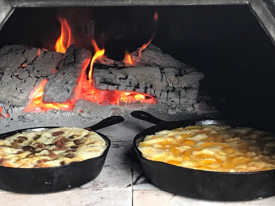 Peach and fig cobbler baked in cast iron skillets inside a wood fired pizza oven