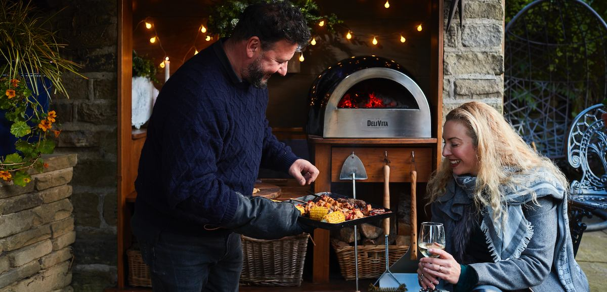 Man and Woman cooking in a DeliVita Wood Fired Pizza Oven