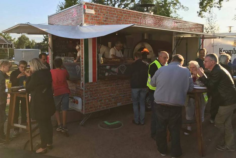 People ordering from a Pizza oven trailer at a food festival