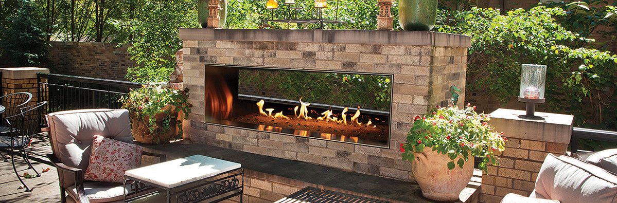 An outdoor gas fireplace from the Carol Rose collection with burning flames