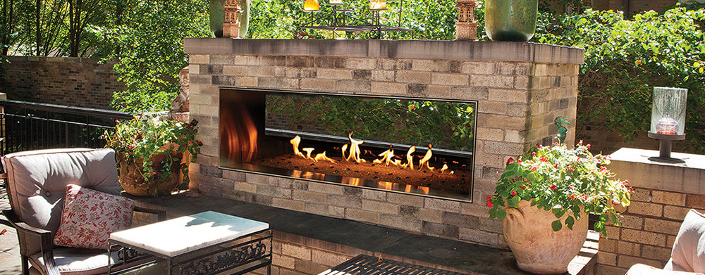 Outdoor gas fireplace burning orange flames on the patio