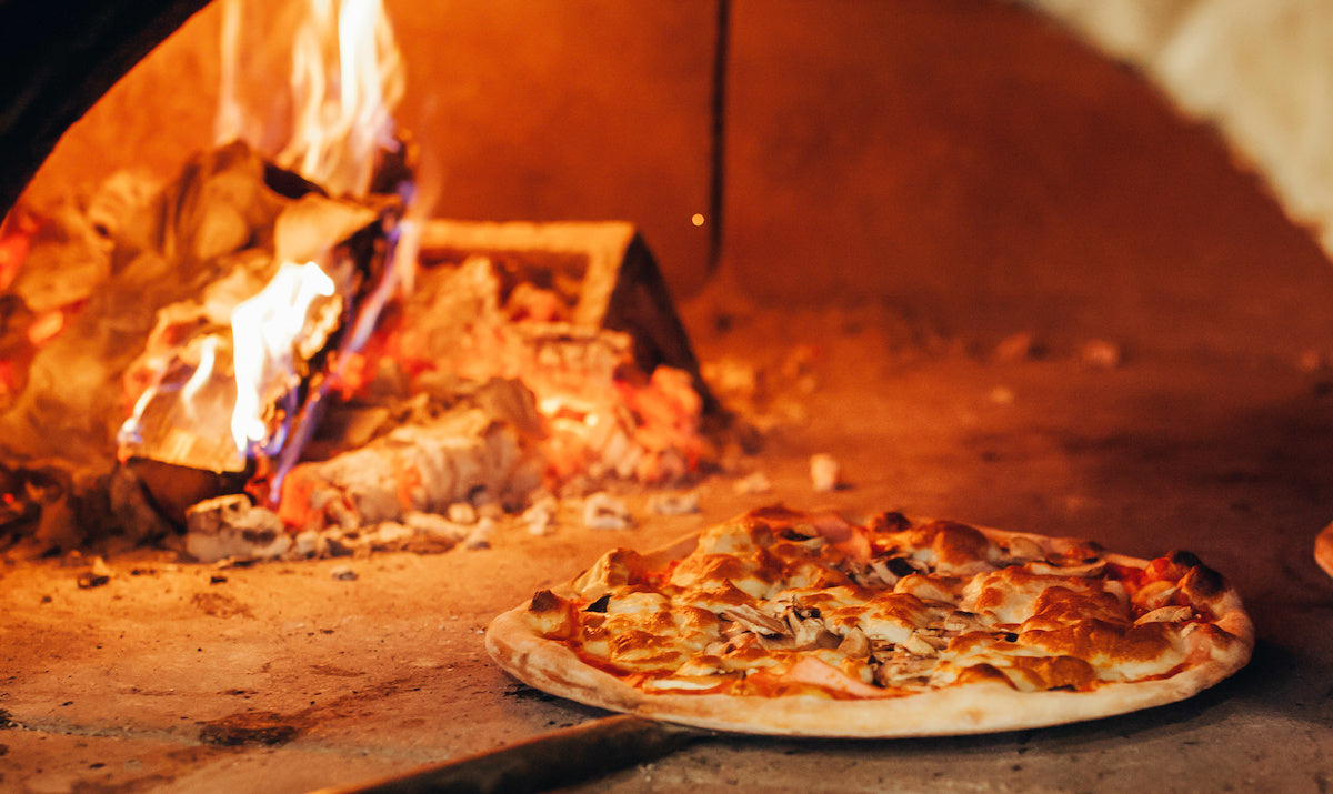 Pizza on a peel in a wood fired oven