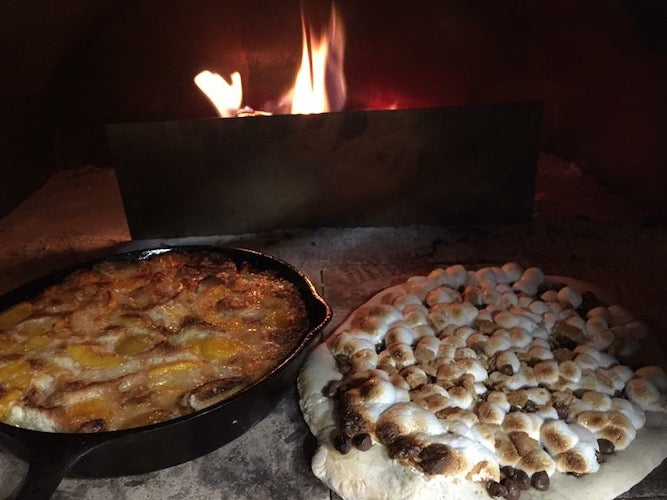 Peach cobbler and s'mores cooking in pizza oven