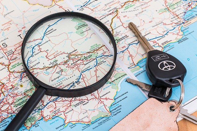Map with car keys and a magnifying glass