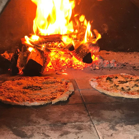 Pizzas cooking in pizza oven