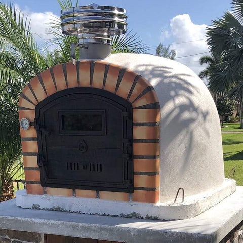 Lisboa Brick Pizza Oven sitting on a backyard custom base