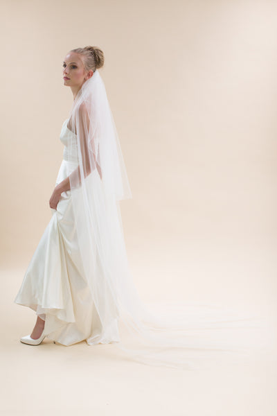 Rainbow Club's Petunia is a romantic two tiered full length veil with an ivory stitched edge