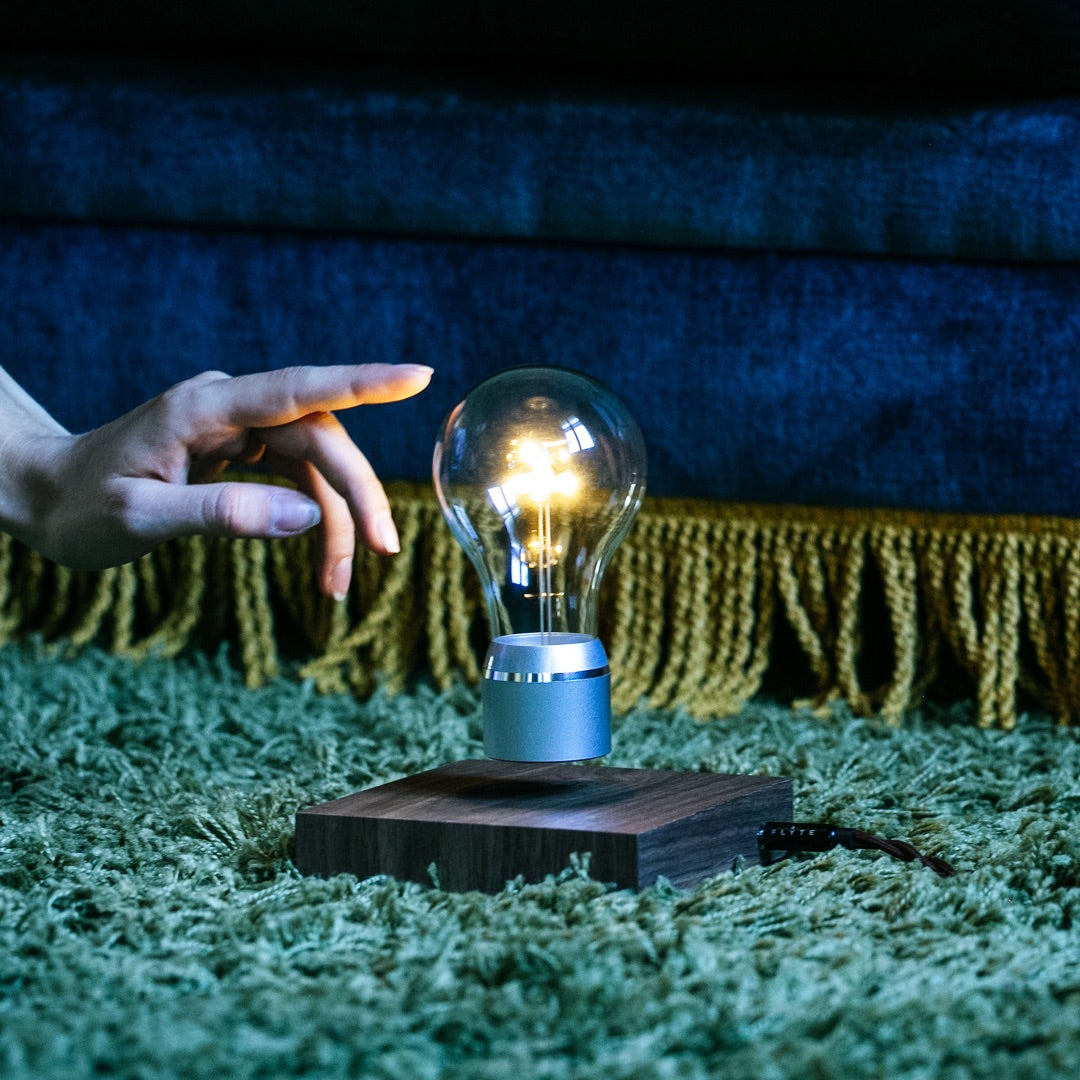 Levitating light bulb Manhattan on carpet with finger reaching to it