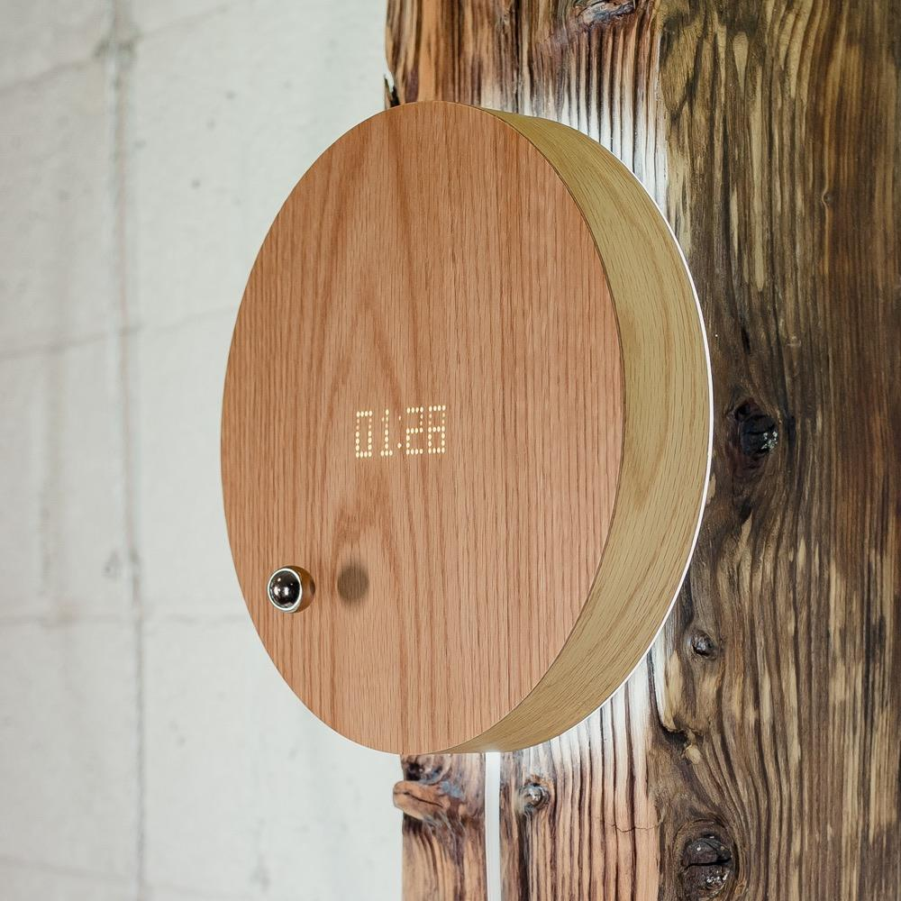 Story oak - side view of levitating clock hanging on the wall with LED display and backlight turned on