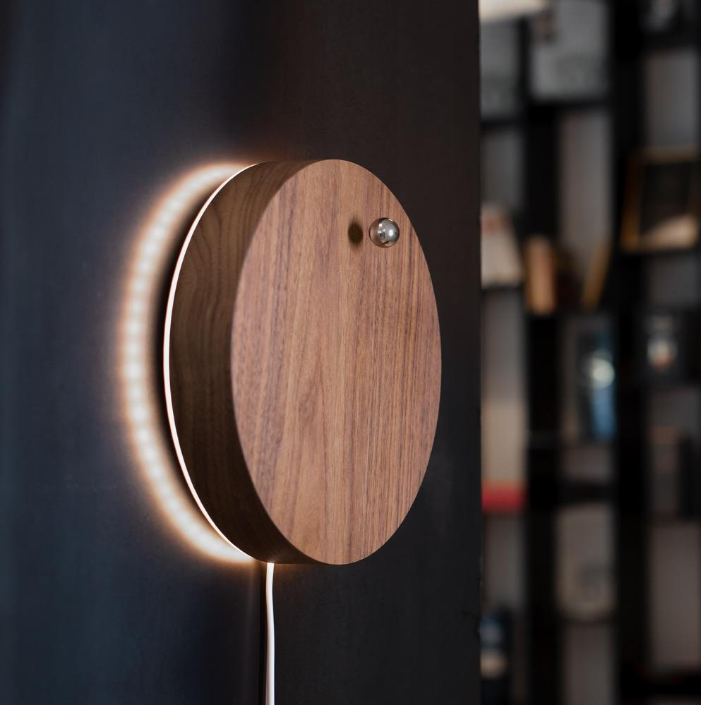Story walnut - side view of levitating clock hanging on the wall with backlight turned on
