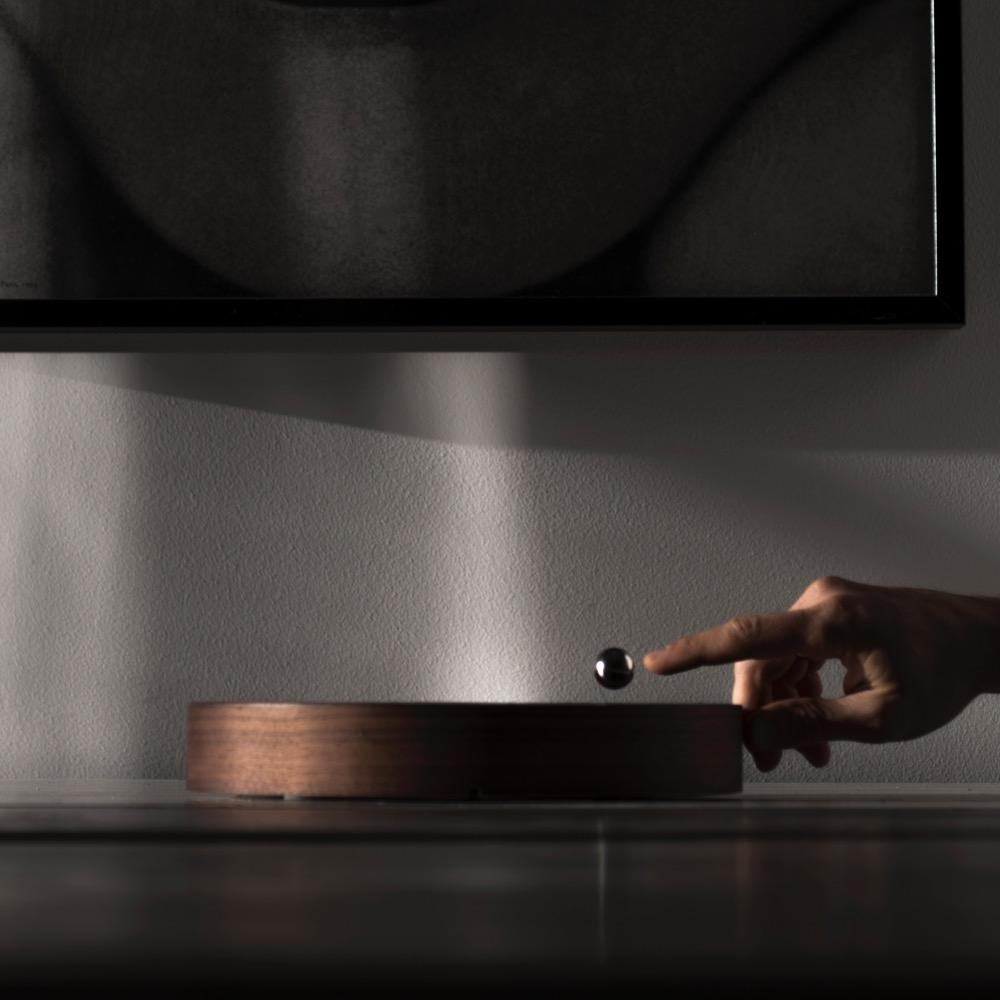 Walnut Story - levitating clock horizontally on the table with ball hovering in the air