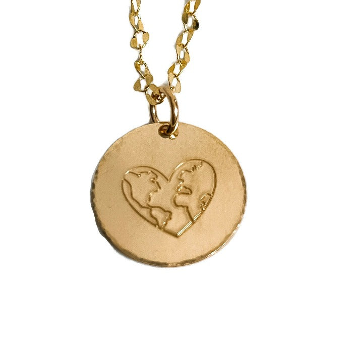 A  gold filled world of love necklace with a  gold filled link chain on a white background and