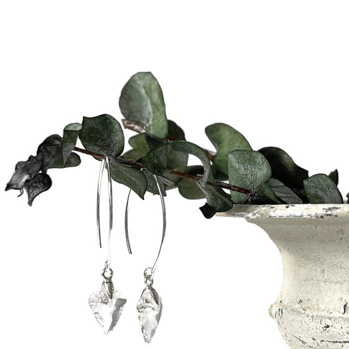Brave Heart clear crystal earrings hanging from a eucalyptus branch