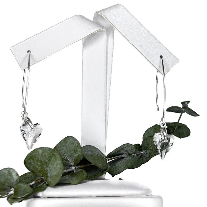 Brave Heart clear crystal earrings hanging with a eucalyptus branch and hanging from a earring holder
