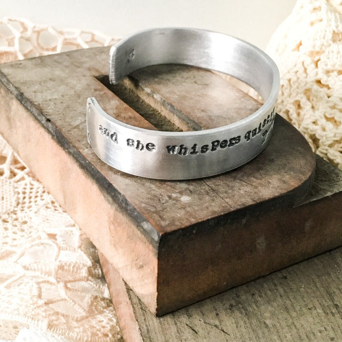 "1/2"" Aluminum cuff hand stamped with ""and she whispers...I am the storm"""