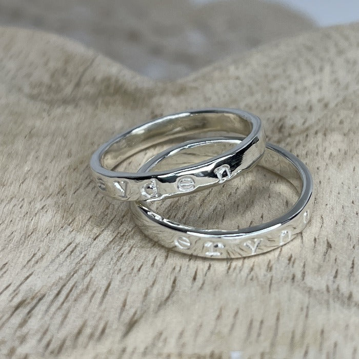 Two sterling silver Inspiration rings with kids name hand-stamped on the bands.  The names are not darkened