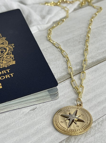 The Roam Necklace laying beside a passport, gold filled and sterling silver compass medallion