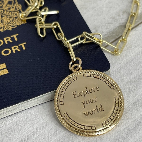 The Roam medallion necklace is inscribed on the back with Explore Your World.  Necklace is laying on a passport.