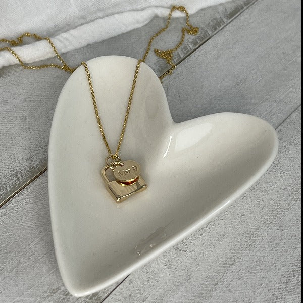 Gold Paris Love Locks Necklace laying in a heart shaped dish