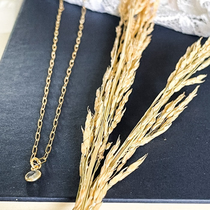 Gold Addie Choker with clear crystal laying on a navy book with wheat