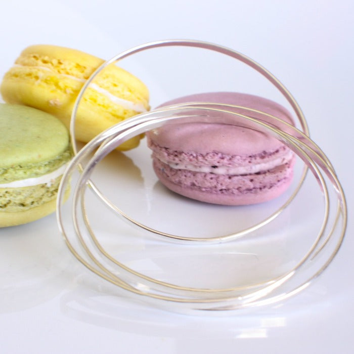 Stack of sterling bangles leaning against a pink macaron