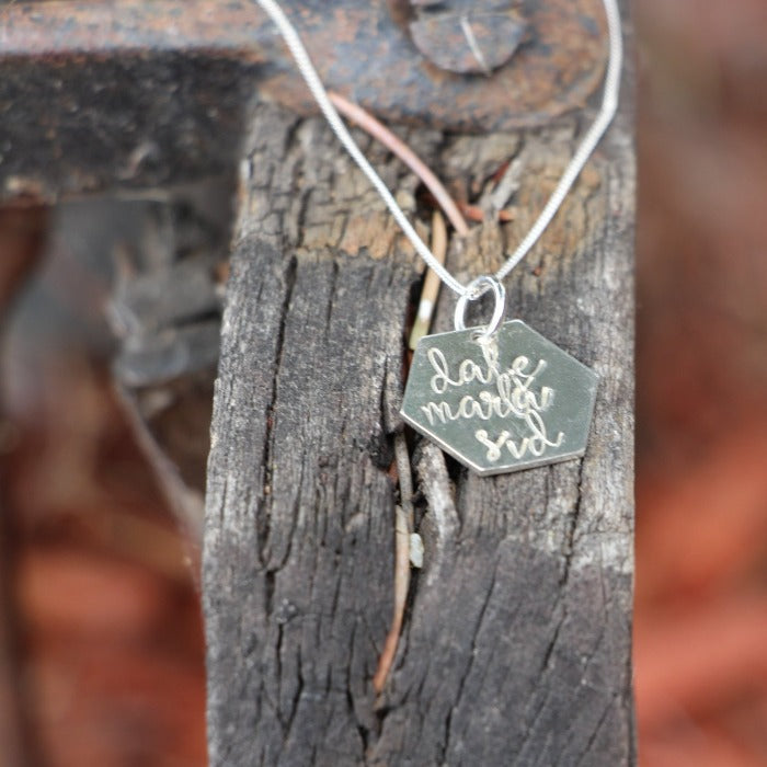 Hexa Necklace with three names hand stamped on it laying on some wood