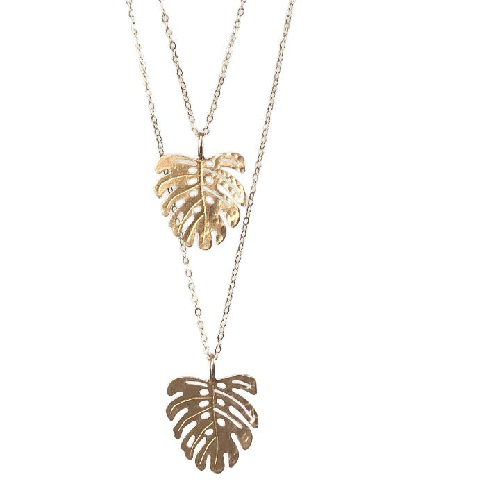 Two Hammered gold Monstera Leaf necklace hanging at different lengthswith white background