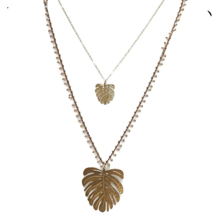 Hammered gold Monstera Leaf necklace with white background