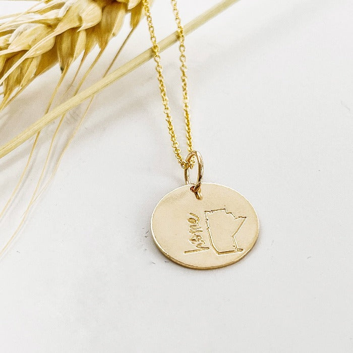Gold Filled Mini Manitoba necklace laying on a stem of wheat
