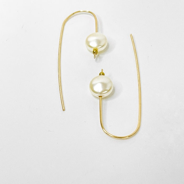 Delicate gold earwires have been hand formed and adorned with freshwater coin pearls, laying on a white background