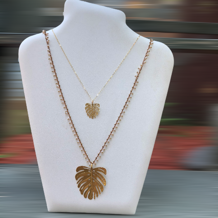 Two gold Monstera Leaf necklaces on jewelry display