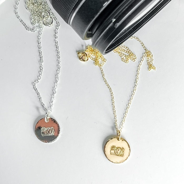 Pretty Pictures Camera Necklace in both silver and gold filled in front of  camera lens