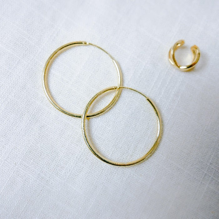 Gold filled hoops laying on linen