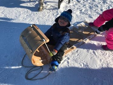 child on wooden toboggan sled